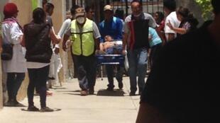 Un blessé arrive sur un brancard à la paroisse d'Asunción Nochixtlán, où ont été soignés de nombreux blessés dimanche. Photo postée sur Twitter par @zanamanza2.