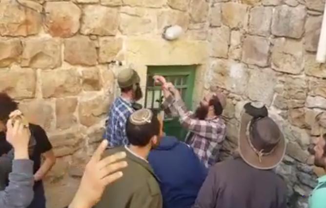 Israeli settlers force open the doors of Palestinian homes in Hebron. Screengrab of video.
