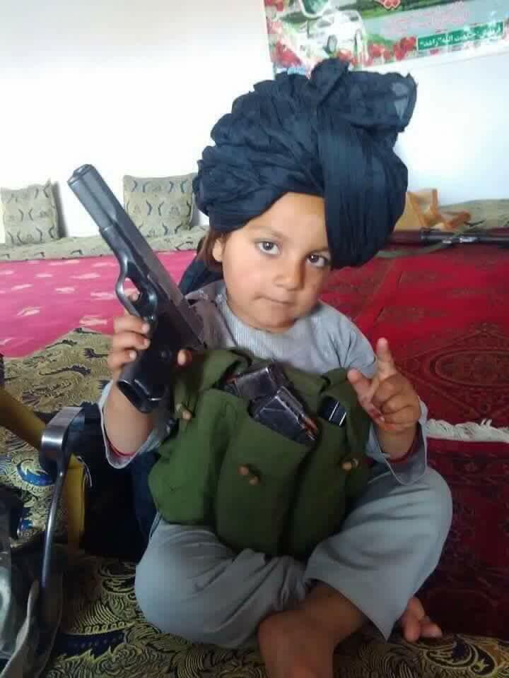 Photo posted by an Afghan journalist on Twitter, showing a young child holding a real handgun.