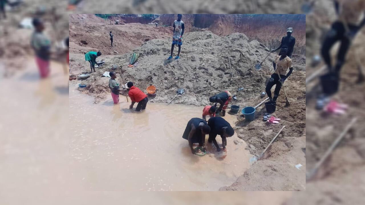 Des personnes en train de laver des minerais dans un étang d'eau.