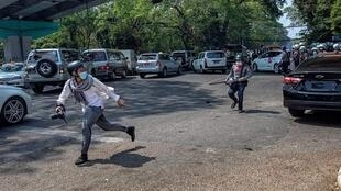 This photo, widely shared on social media, shows a Myanmar policeman chasing a journalist holding a camera in Yangon on February 26, 2021.