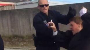"""Capture d'écran d'une vidéo envoyée par l'association """"L'auberge des migrants"""" montrant un CRS en train de pousser une bénévole en train de filmer l'intervention policière."""