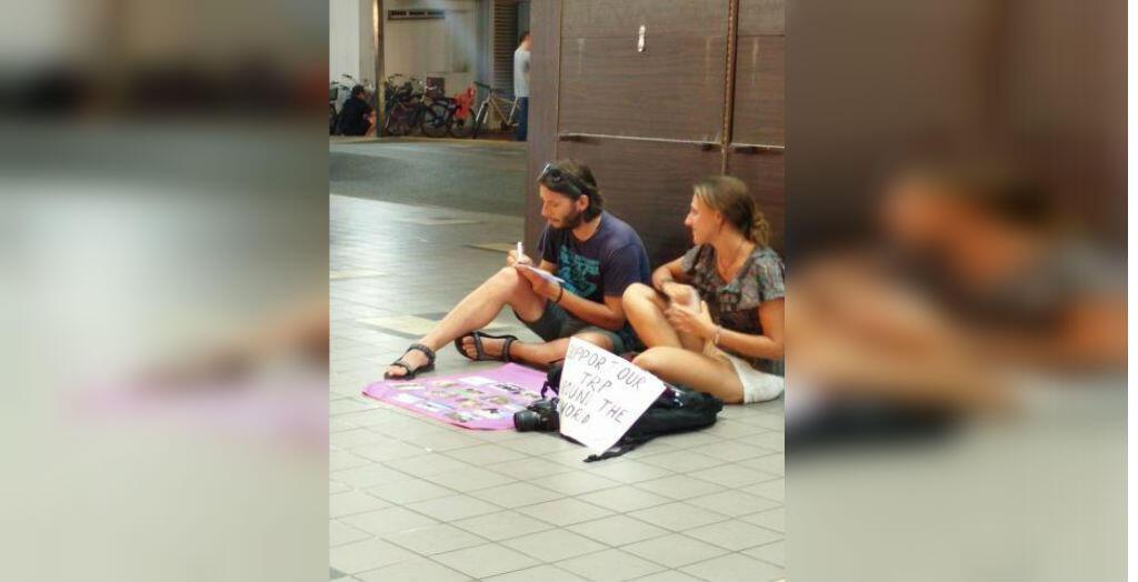 Jeune couple en train de vendre des cartes postales pour financer le tour du monde. Photo publiée sur Twitter.