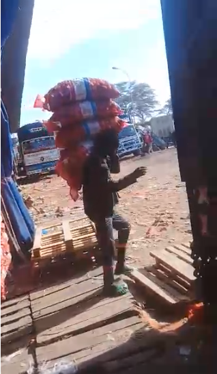 A porter carries wares. (Screengrab of a video filmed by our Observer Camara Mahmoud.)