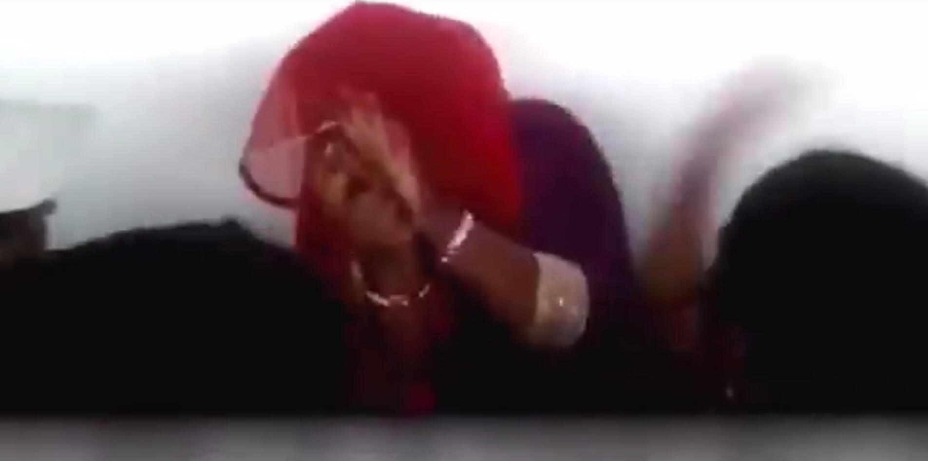A woman, accused of tansporting beef, tries to protect herself from a mob. Screen grab from the video below.