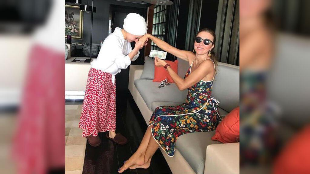 La photo montre la femme du ministre de la Culture et du Toursime, à droite, en train de recevoir un baiser et de donner 100 dollars à l'une de ses employées.