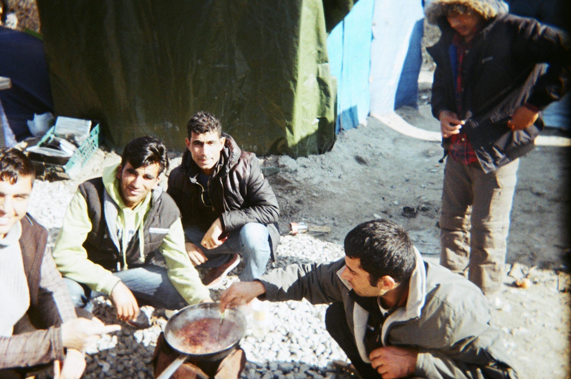 Des refugiés réchauffent leurs plats avec les moyens du bord.