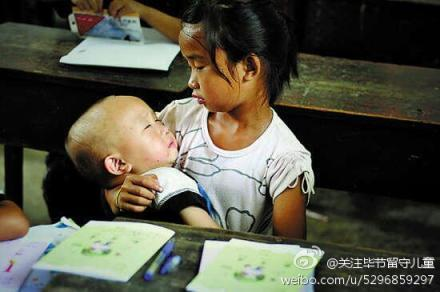 A young girl, forced to live without her parents, looks after her little brother in class. Photo uploaded to the shared Weibo account of NGOs dedicated to helping the children of migrant workers in China.