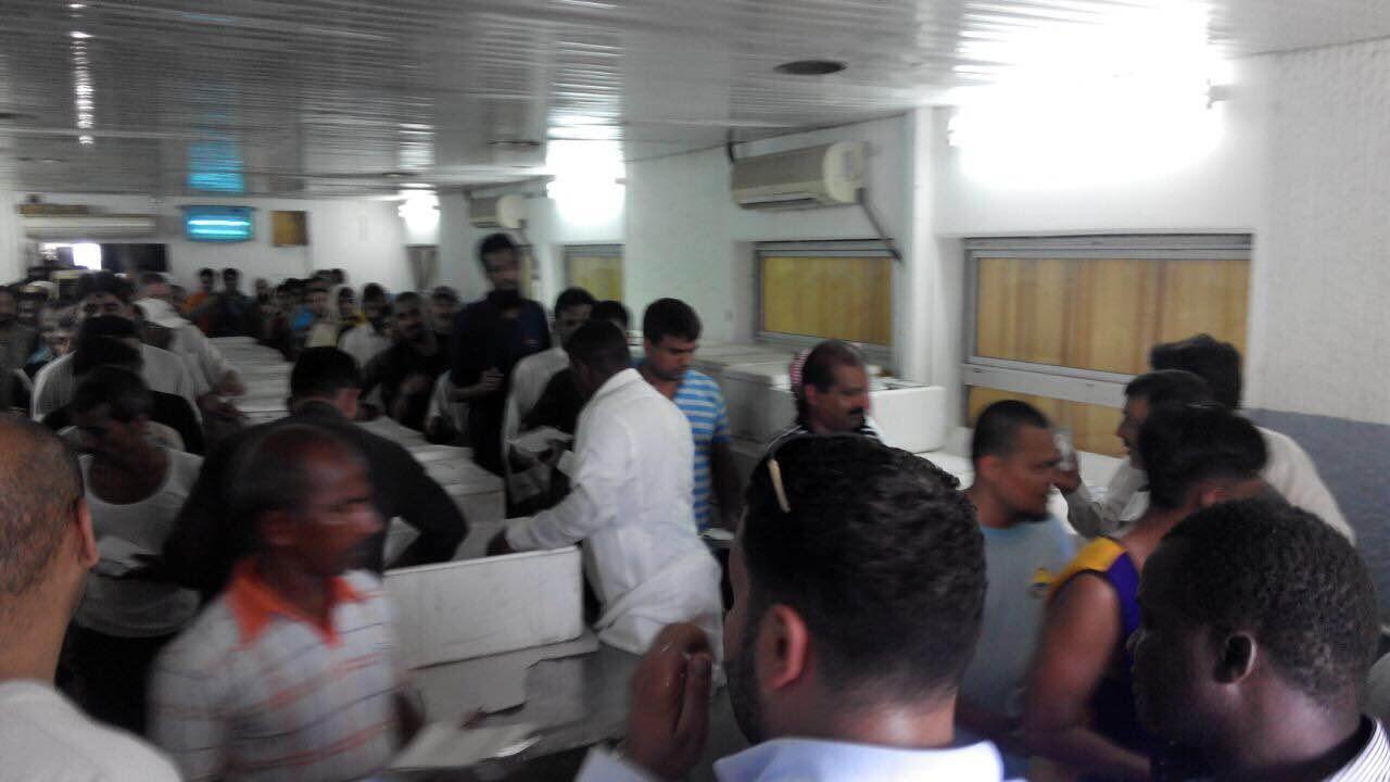 Des travailleurs étrangers dans un camp géré par leur entreprise, à Djeddah, reçoivent de la nourriture de la part d'ONG.