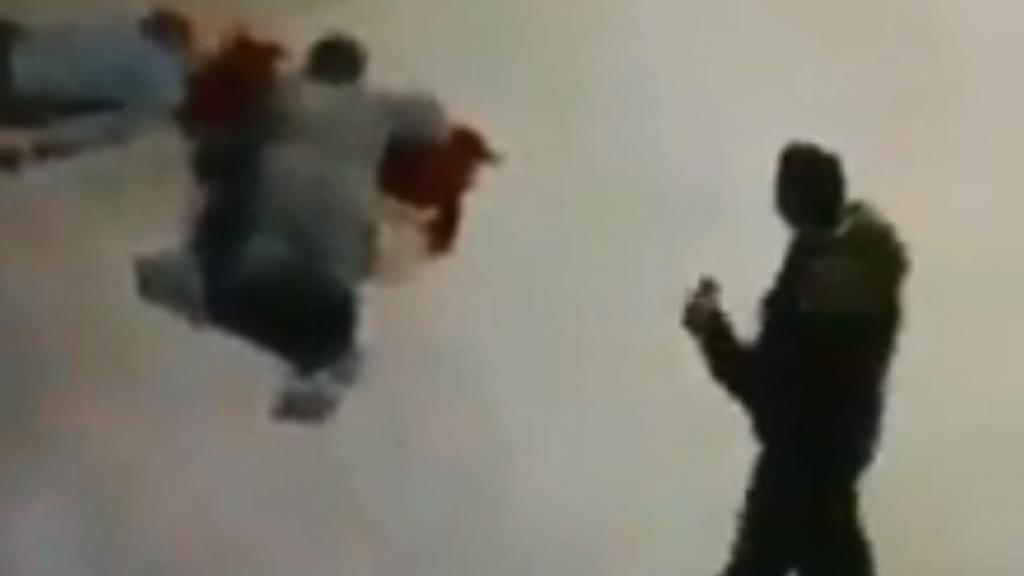 A policeman stands next to two Coptic Christian men who he allegedly shot and killed (screengrab from video).