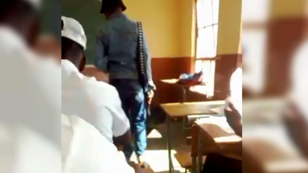 Un enseignant muni d'un pistolet surveille la classe lors d'un examen.