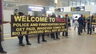 """Des policiers brandissant une banderole """"bienvenue en enfer"""" dans l'aéroport international de Rio. Photo publiée sur le site de partage d'images Imgur et vue près de 3 millions de fois."""