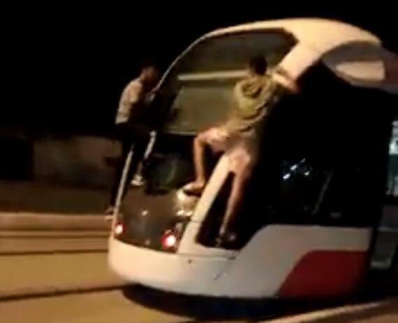 """صورة شاشة من فيديو يظهر فيه شابان متعلقين بمؤخرة قطار """"تراموي"""" مدينة وهران الجزائرية"""