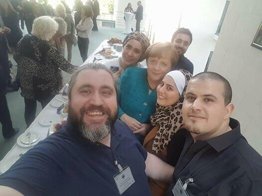"""Mallakeh Jazmati, un des membres du groupe """"Cuisine d'exil"""" et ses amis avec la chancellière allemande Angela Merkel."""