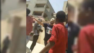 A member of Libyan security forces is seen shoving a Sudanese refugee in Tripoli in a video shared online. (@Sudan_Asrf/Twitter)
