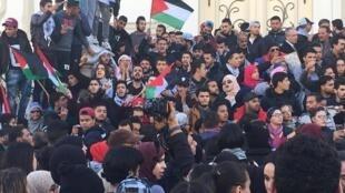 متظاهرون في الشارع الرئيسي لتونس العاصمة يرفعون أعلاما فلسطينية احتجاجا على اعتراف دونالد ترامب بالقدس عاصمة لإسرائيل.