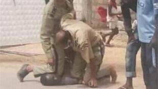 Two Mauritanian police officers hold a Black man on the ground, facedown. One of the officers has his knee pressed into the man's neck.