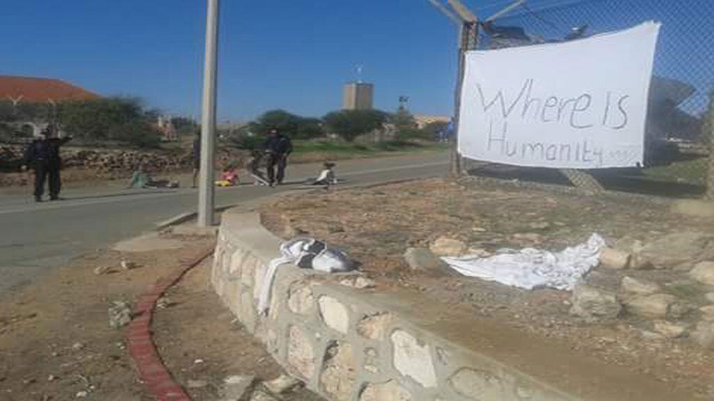 """""""Where is humanity?"""" reads this sign, which sits in front of a camp of refugees located on a British military base in Cyprus."""