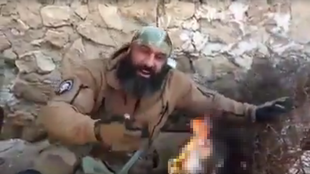 """Abou Azrael, also known as the """"Iraqi Rambo"""", burning the beard of a jihadist fighter who was killed by the Rambo's Shiite militia."""