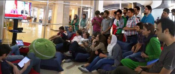 Des employés d'une start-up en Iran se rassemblent pour regarder l'annonce de l'accord à la télévision.