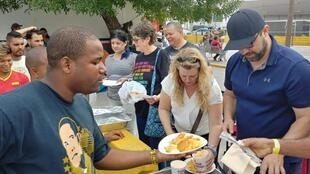 Team Brownsville volunteers serve meals to asylum seekers in Matamoros, Mexico. (Courtesy of Team Brownsville)