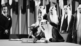 Le prince Fayçal signant la charte des Nations unies en 1945 accompagné d'un petit bonhomme vert.