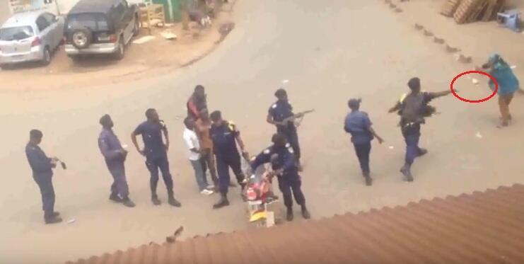 Un policier congolais jette une pierre sur une femme dans un quartier où est implanté un marché à Bukavu. Capture d'écran vidéo ci-dessous.