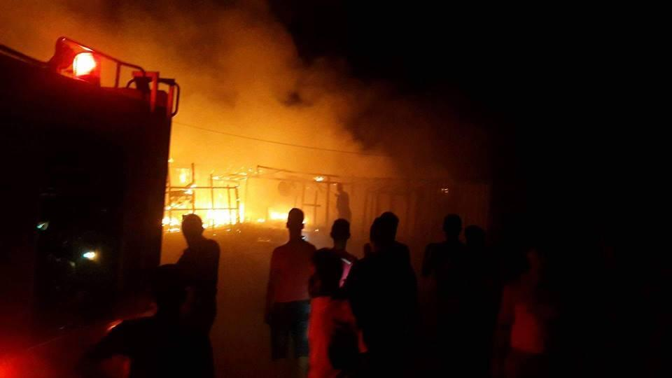 Des personnes regardent les tentes brûlér dans le camp de Hosnyeh dans le Akkar (Akkar News Network)