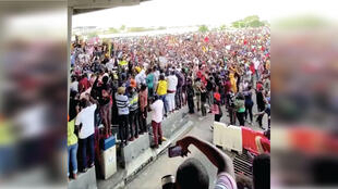This screenshot of an October 14 Twitter video shows a crowd of Nigerian #EndSARS protesters singing at Lekki Toll Gate in Lagos. However, other peaceful protests in the country have been upended by police violence.