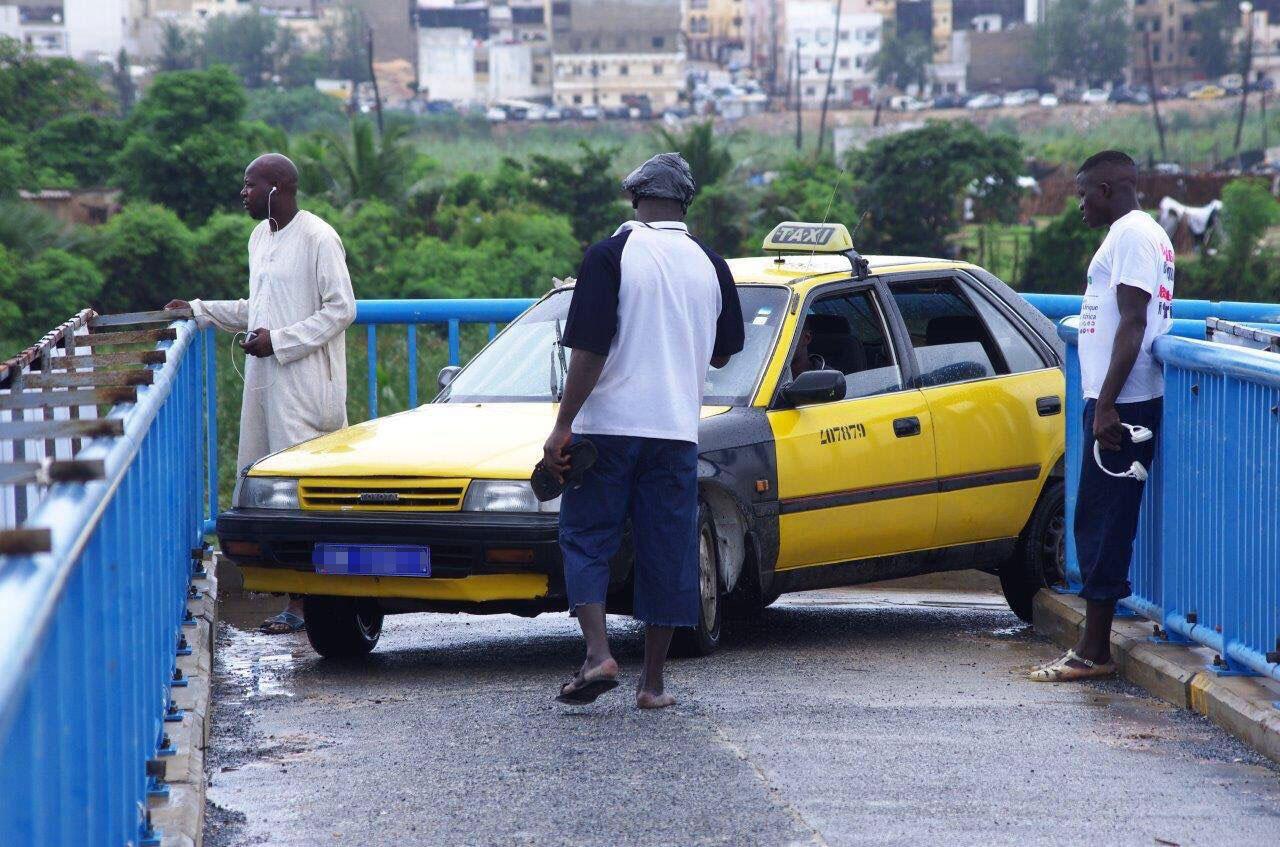 Un taxi dakarois s'engage sur une passerelle réservée au piéton le 9 aout. Toutes les photos ont été prises par Romuald Taylor pour Au-Senegal.com.