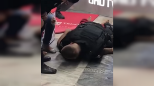 This video shows a security guard using his entire body to pin a young man to the ground. The guard suspected the young man of wanting to steal his gun. The young man died as a result of this assault. (Screengrab from YouTube)