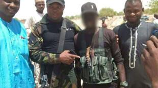 """Un membre d'un """"comité de vigilance"""" de Gambaru, au Nigeria, aux côtés d'un militaire camerounais du Bataillon d'intervention rapide (BIR). Toutes les photos ont été envoyées par notre Observateur. Photo floutée par France 24."""