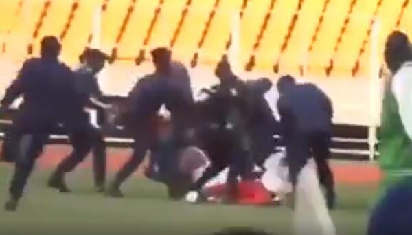 """Des policiers viennent en aide à un arbitre assistant roué de coups par des """"supporteurs"""" mécontents à Kinshasa."""
