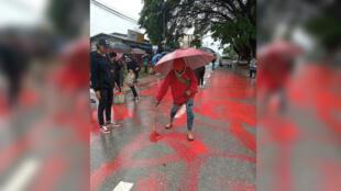 En Birmanie, un manifestant en train de peindre une rue en rouge pour protester contre le coup d'État militaire.