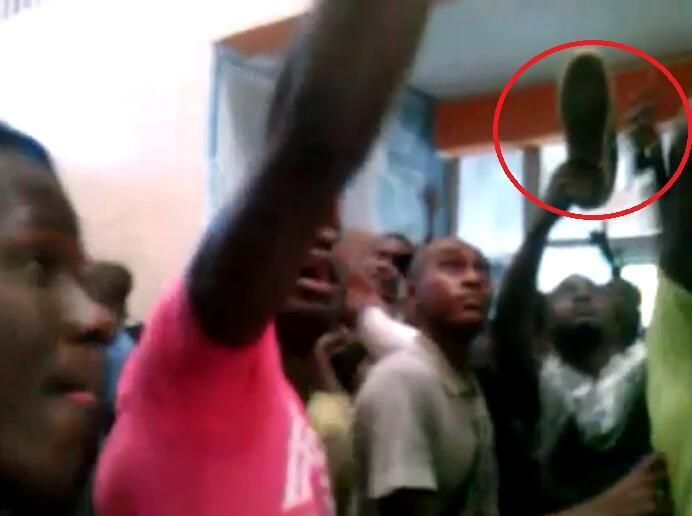 Dakar university students looking for a student accused of hitting on another man. One young man brandishes a shoe in the air, apparently to hit the student with it.