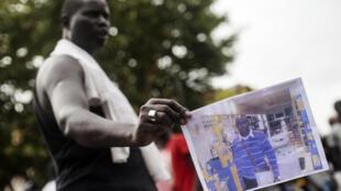 Ce Sénégalais montre une photo de son compatriote décédé le 11 août quelques heures plus tôt, lors d'une opération policière. Crédit : Robert Bonet.