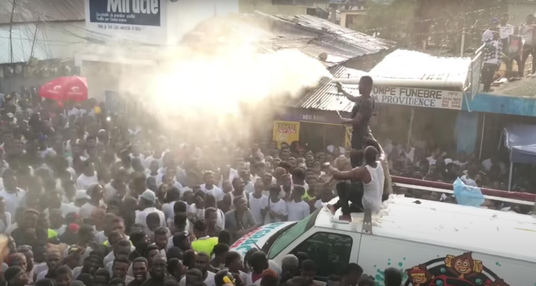 """Une foule de personnes à Port-au-Prince se rassemble lors d'un """"car wash"""" autour d'un DJ. Capture d'écran de la vidéo Passion Info Plus."""