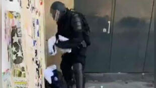 A screengrab from a Brut livestream that shows a police officer putting what appear to be jerseys into his bag.