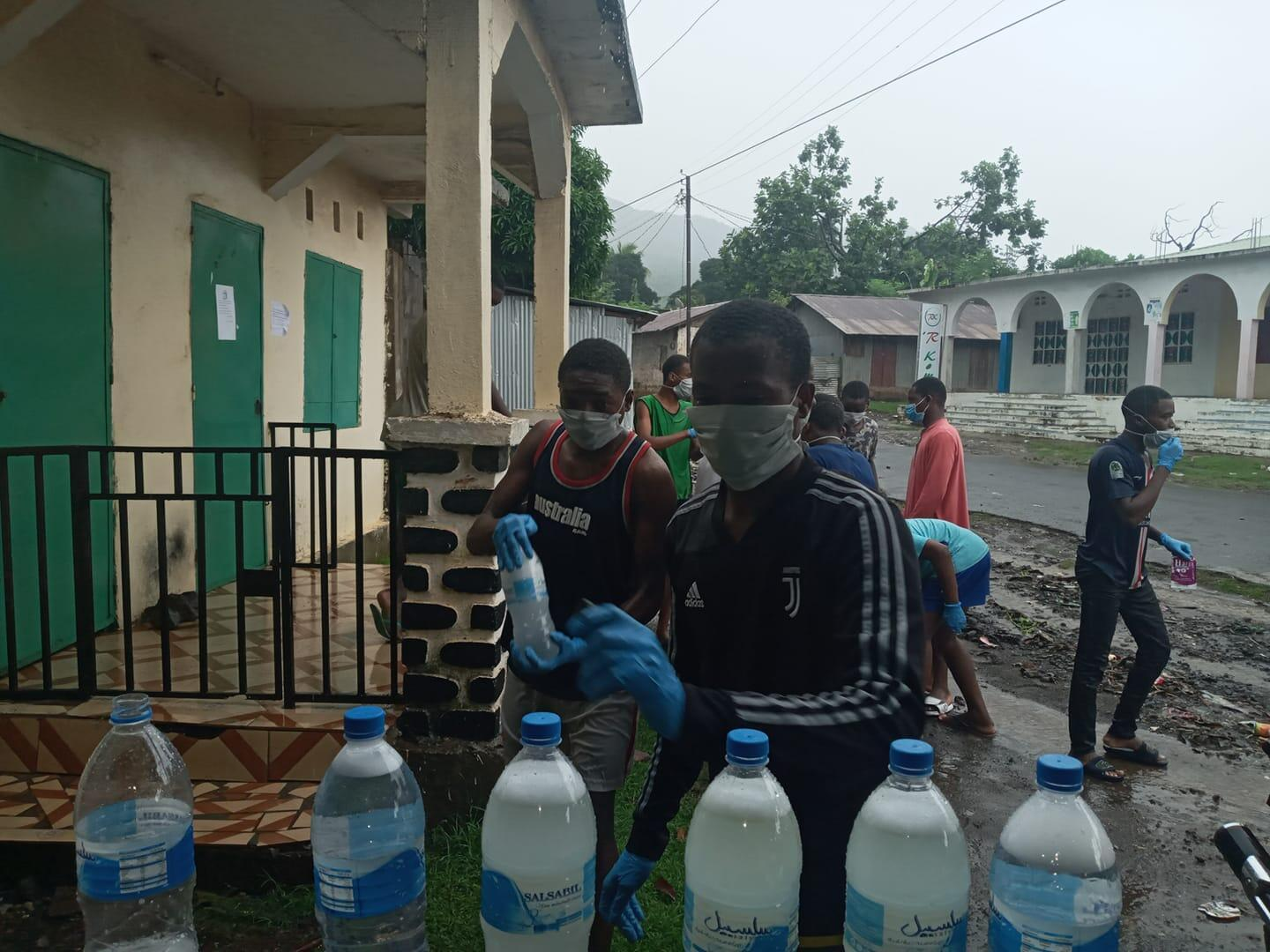 Members of a youth committee hand out disinfectant in Mohéli.