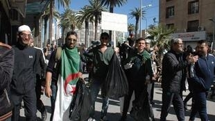 Our Observer, Nacerdinne Rahmoune, and friends posing with rubbish bags during protests in Sidi Bel Abbès, Algeria.