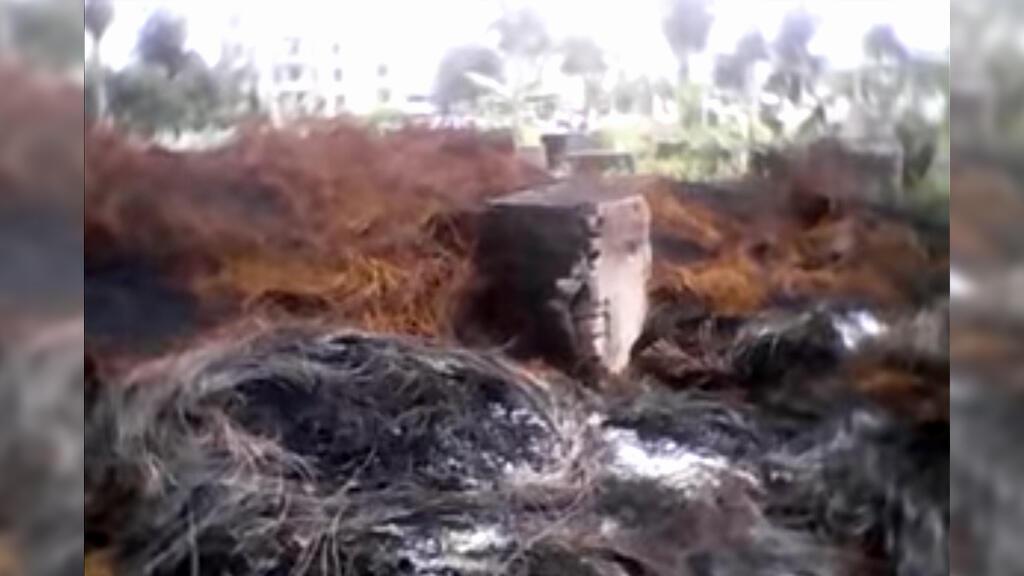 Devant les pierres tombales, des carcasses de pneus et des fils de fers brûlés se mêlent aux hautes herbes. Photo Christophe Nyemeck.