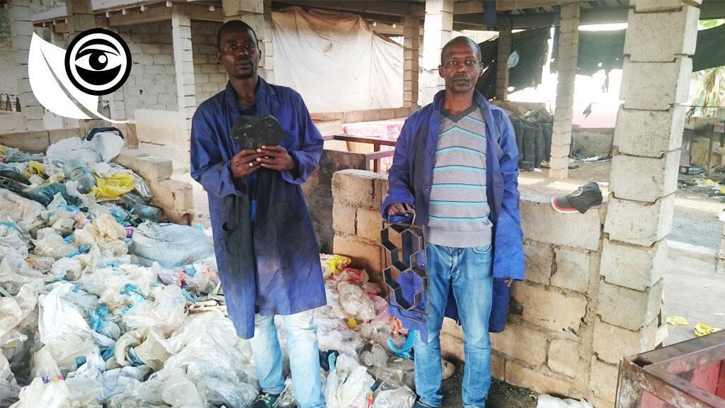 Deux employés avec les pavés et derrière eux, les déchets plastiques grâce auxquels ils sont produits.