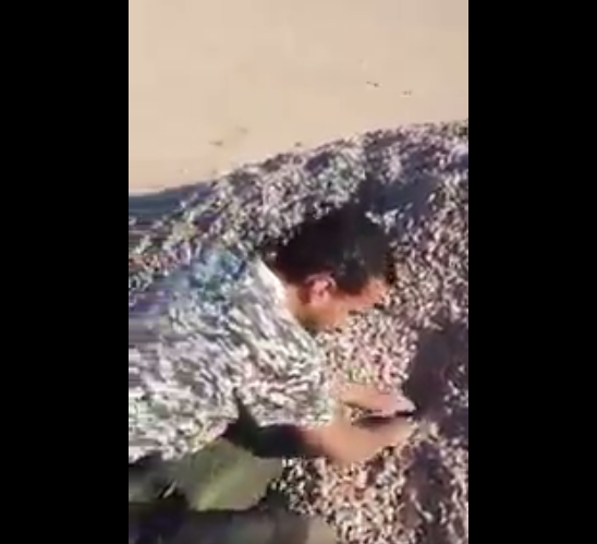 A soldier from the Libyan National Army disarms an artisanal mine with his bare hands.
