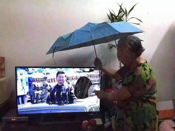 Une vieille dame devant sa télévision regarde le président Xi Jinping, l'évente et le protège du soleil avec un parapluie.
