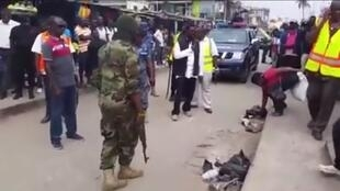 The mayor of Accra (who's pictured in the centre of the photo wearing black and white) orders market vendors (pictured right) to pick up their trash, under the watchful eyes of armed soldiers.