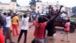 """Des Banguissois agitent les bras en criant """"non"""" ou en huant au passage de soldats français de la force Sangaris."""