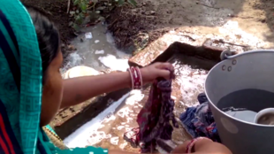An Indian woman washes bits of cloth used to soak up her blood during her period. Screen capture from a video by Video volunteers.