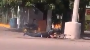 A cartel gunman fires a high calibre rifle, screenshot from a video posted on Twitter, October 17.