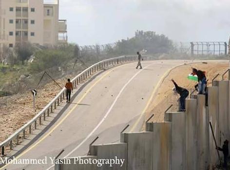 Des jeunes palestiniens franchissent le mur à Bil'in. Photo de notre Observateur.