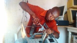 Cette imprimante 3D a été fabriquée à partir de déchets électroniques, comme une carcasse de scanner, récupérés dans des décharges de Lomé. Elle vient de fabriquer un gobelet en plastique. Photo Afate Gnikou.